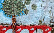 طفل يجلس أمام لوحة جدارية تمثل فيروس كورونا المسبب لمرض كوفيد -19 في بوكور، جاوة الغربية بإندونيسيا، 27 سبتمبر 2020