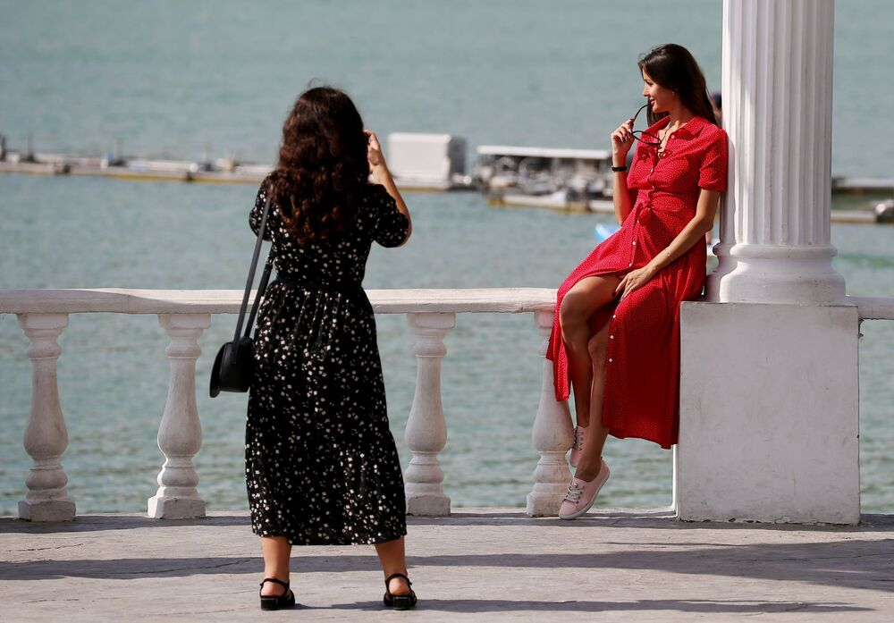 فتاتان تلتقطان صورا على خلفية شاطئ بحيرة أبراو في إقليم كراسنودار الروسي، 27 سبتمر 2020