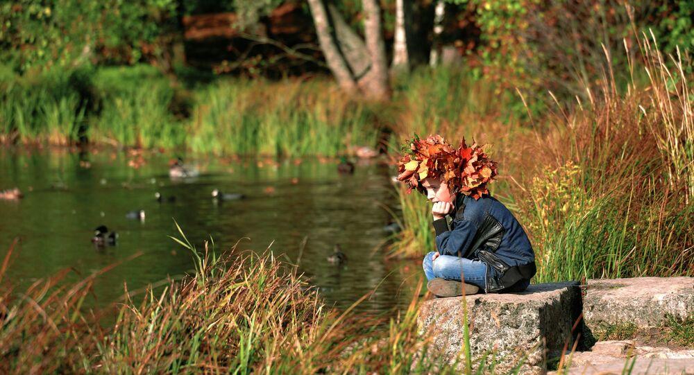 طفل يجلس على ضفاف بحيرة بيلويه في الحديقة العامة في بلدة غاتشينا، إقليم لينينغراد، روسيا 27 سبتمبر 2020