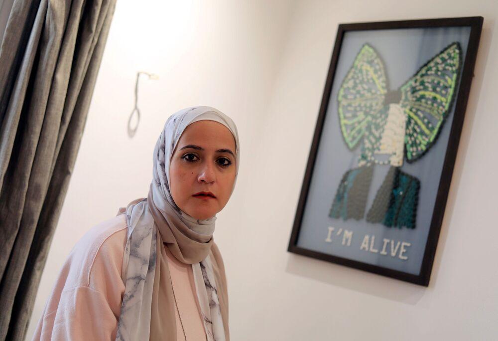 الفنانة المصرية أمل صلاح (35 عاما)، تقف على خلفية لوحة بعنوان I'm Alive (أنا حي) في منزلها، القاهرة 6 أكتوبر 2020