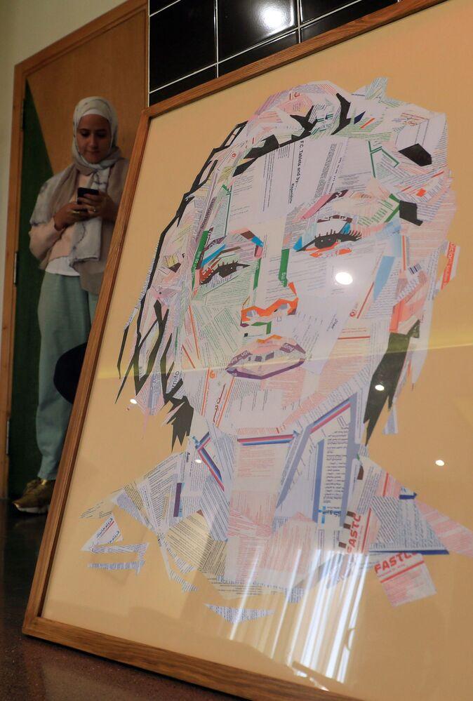 الفنانة المصرية أمل صلاح (35 عاما)، تقف على خلفية لوحة للمغنية الأمريكية Madonna (أنا حي) في منزلها، القاهرة 6 أكتوبر 2020
