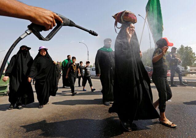 يتم رش الحجاج الشيعة العراقيين بالماء لتبريدهم أثناء توجههم إلى مدينة كربلاء، وذلك قبل طقوس أربعينية الحسين، وسط تفشي فيروس كورونا في بغداد، العراق، 5 أكتوبر / تشرين الأول 2020.