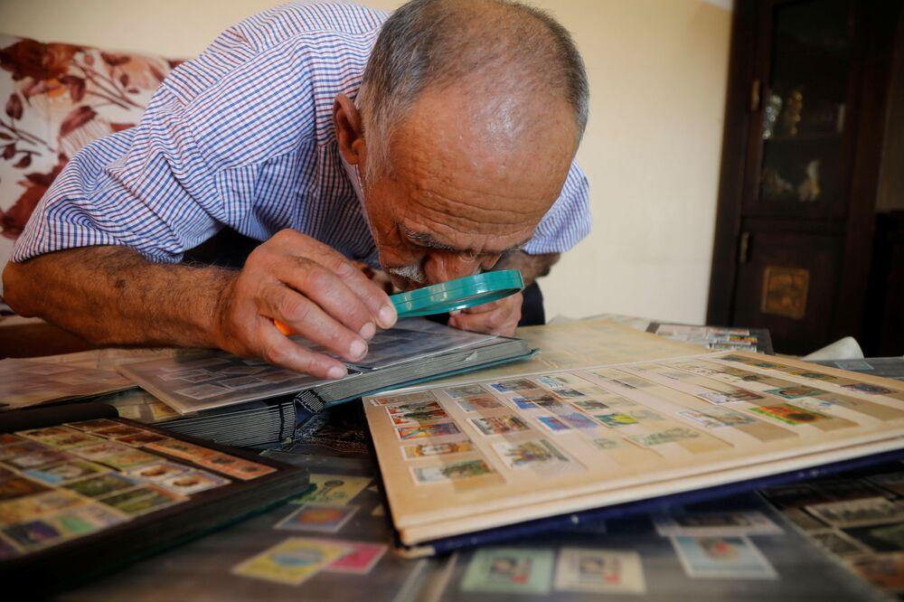الفلسطيني محمود كايد، يعرض مجموعته من طابع البريد، التي يجمعها منذ عقود، في بلدة فلسطينية تقع في محافظة نابلس، الضفة الغربية، 7 أكتوبر 2020