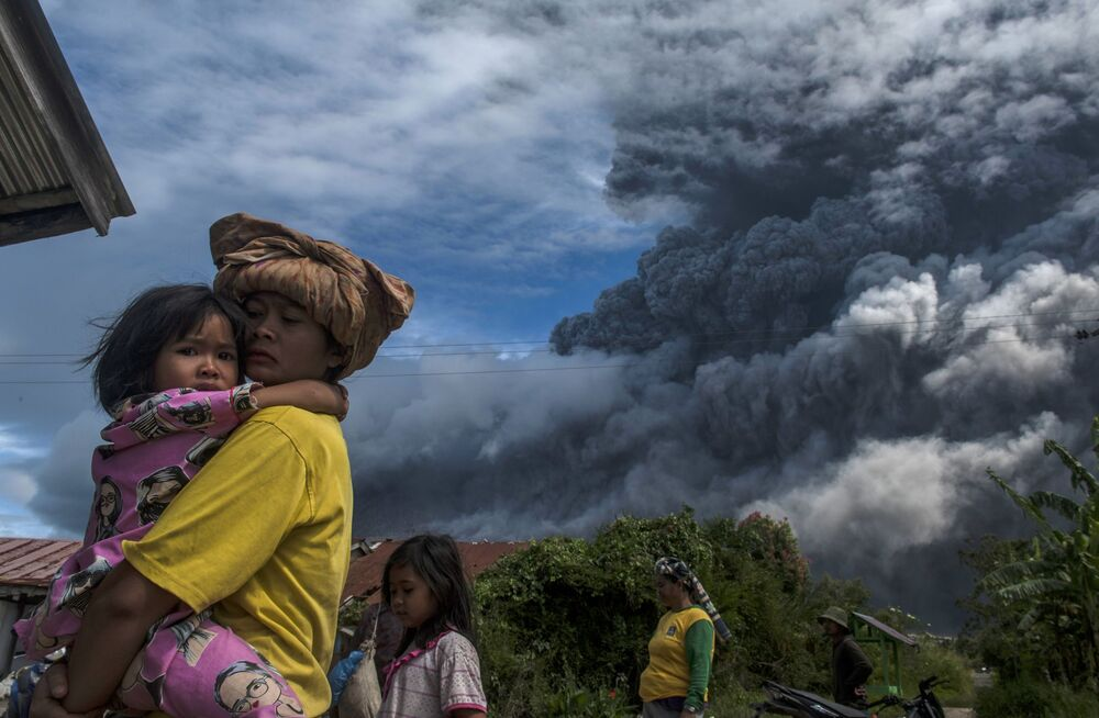 المواطنون الإندونيسيون المقيمون بالقرب  من بركان سينابونغ النشط، شمال جزيرة سومطرة، إندونيسيا 10 أغسطس 2020