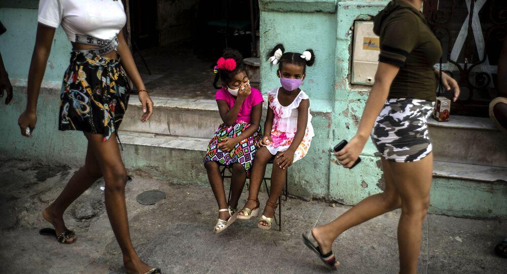 طفلتان ترتديان كمامات كإجراء احترازي ضد انتشار فيروس كورونا، تنتظران والديهما لأخذهما خارج المنزل في هافانا، كوبا، 12 أكتوبر 2020