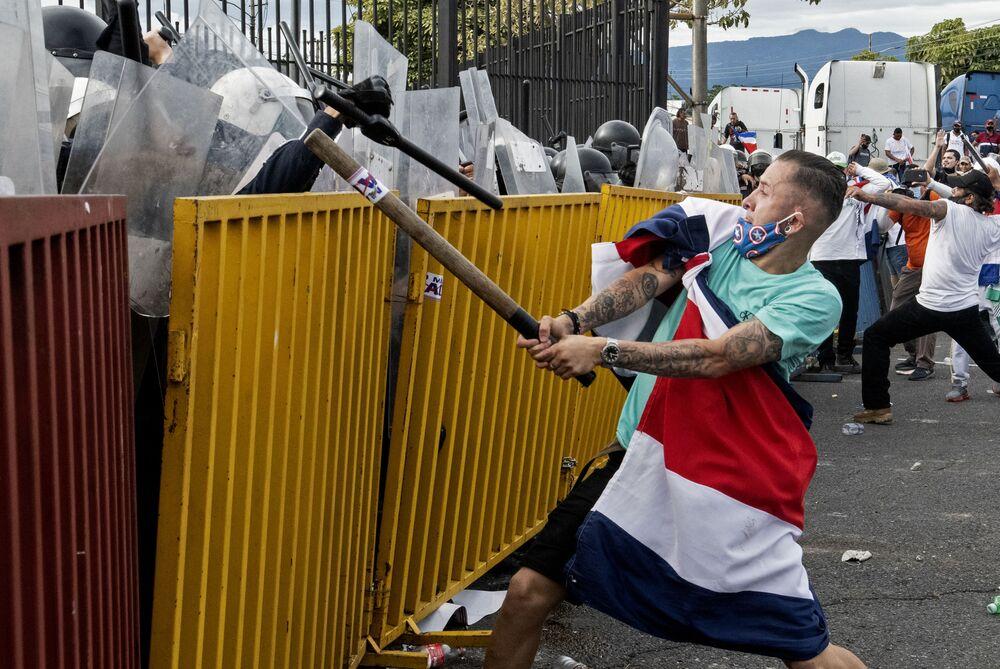 متظاهر يضع علم كوستاريكا يحمل أنبوبا معدنيا، يواجه شرطة مكافحة الشغب خلال احتجاجات على مقترح الحكومة بزيادة الضرائب في غطار التوصل إلى اتفاقية ائتمان مع صندوق النقد الدولي (IMF) ، خارج المقر الرئاسي في سان خوسيه، كوستاريكا في 12 أكتوبر 2020