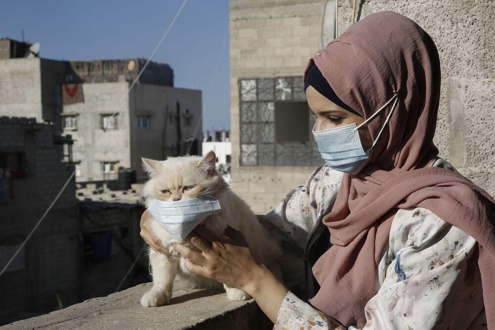 الفنانة الفلسطينية خلود الدسوقي وقطتها على سطح منزلها خلال الإلاق التام في مدينة خان يونس جنوب قطاع غزة، وسط قيود مشددة بسبب تفشي جائحة كوفيد -19، 12 أكتوبر 2020