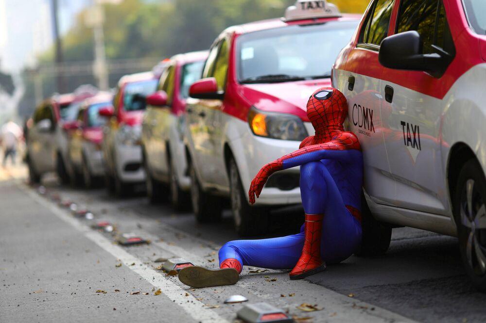 شخص يرتدي زي الرجل العنكبوت يجلس بجوار سيارات الأجرة بينما يحتج سائقو سيارات الأجرة على إطلاق تطبيقات جديدة لاستدعاء سيارات الأجرة مثل Uber و Cabify و Didi  أمام النصب التذكاري ملاك الاستقلال في مكسيكو سيتي، المكسيك، 12 أكتوبر 2020
