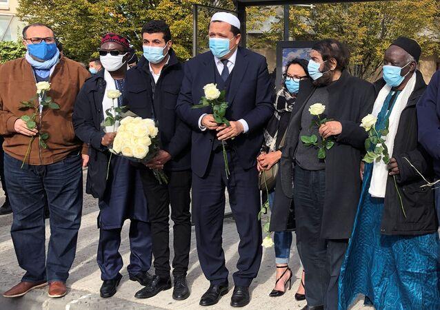 حسن شلغومي، إمام مسجد في درانسي في باريس ضمن وفد من شخصيات إسلامية لوضع باقة من الزهور خارج المدرسة التي قتل عندها المدرس