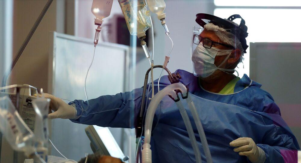 ممرض تفحص مريضا يعاني من مرض فيروس كورونا في وحدة العناية المركزة بأحد المستشفيات في ضواحي بوينس آيرس بالأرجنتين