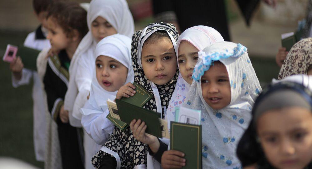 بنات في رياض أطفال من مدرسة بالقاهرة يحملون جوازات سفر وهمية حيث يقومون بمحاكاة الحج إلى مكة.