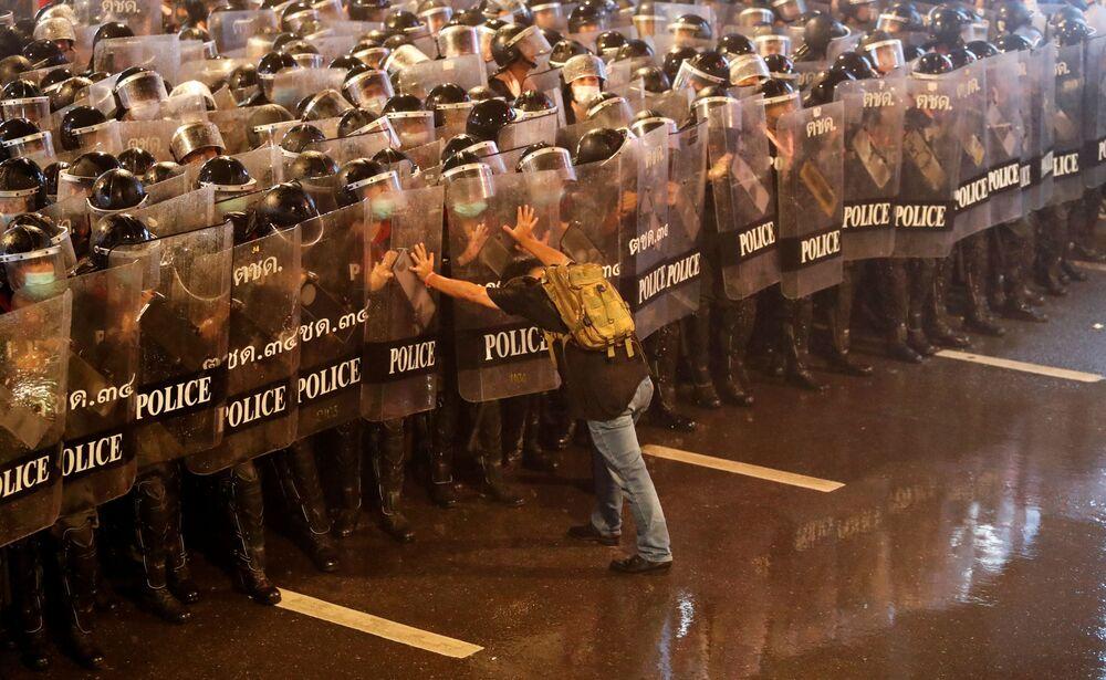 رجل يدفع ضباط الشرطة إلى الخلف أثناء احتجاجات مناهضة للحكومة في بانكوك  تايلاند، 16 أكتوبر 2020.