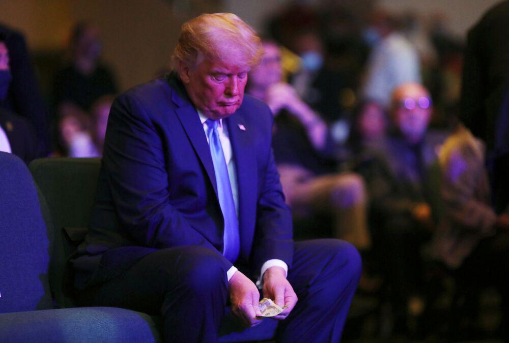 الرئيس الأمريكي دونالد ترامب يخرج بعضاً من المال قبل التبرع في الكنيسة الدولية لاس فيغاس، الولايات المتحدة 18 أكتوبر 2020