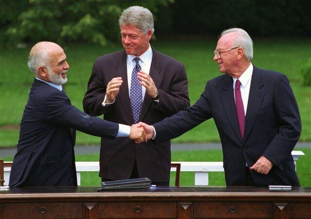 ملك الأردن السابق الملك حسين  يصافح رئيس الوزراء الإسرائيلي إسحاق رابين بعد التوقيع على توقيع اتفاق سلام بينهما عام 1994