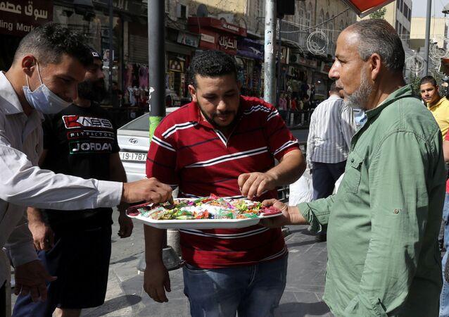 مواطن أردني يقوم بتوزيع الحلو على الزبائن والمارة بمناسبة إحياء ذكرى المولد النبوي في مدينة عمان، الأردن  29 أكتوبر/ تشرين الأول 2020