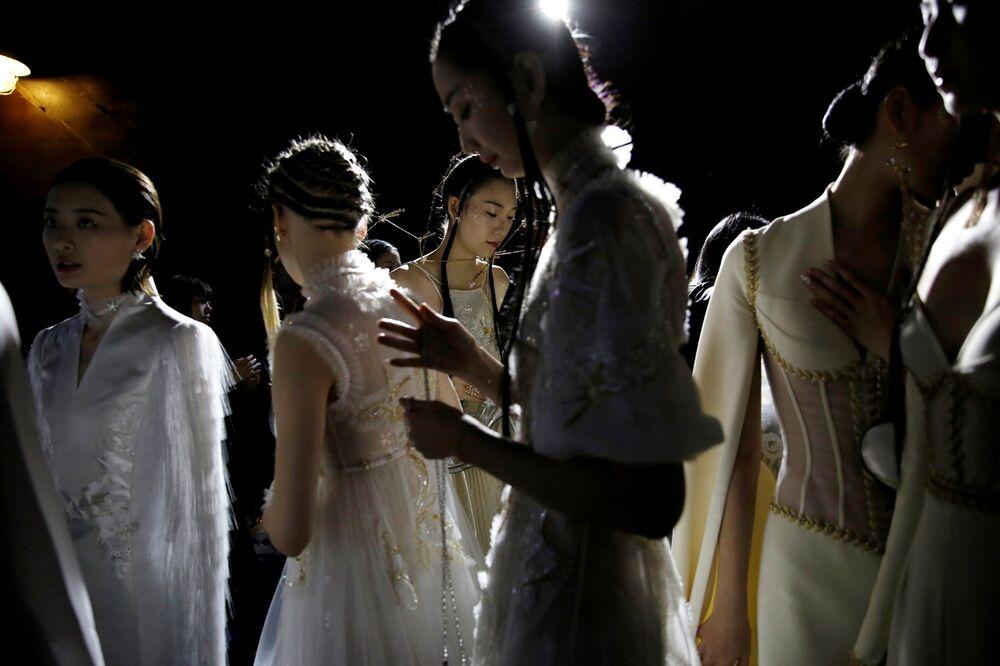 عاضرات أزياء بستعدن للخروج على منصة عرض أزياء هيفن غايا/  مجموعة صيف 2021 من تصميم الصيني شيونغ ينغ، خلال أسبوع الموضة في الصين في بكين، الصين، 24 أكتوبر/ تشرين الأول 2020.