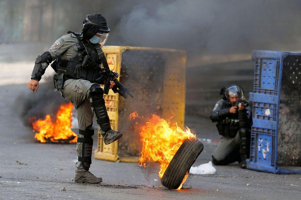 شرطي من حرس الحدود الإسرائيلي يركل عجلة مشتعلة خلال احتجاجات الفلسطينيين ضد إسرائيل في الخليل، الضفة الغربية، 23 أكتوبر 2020