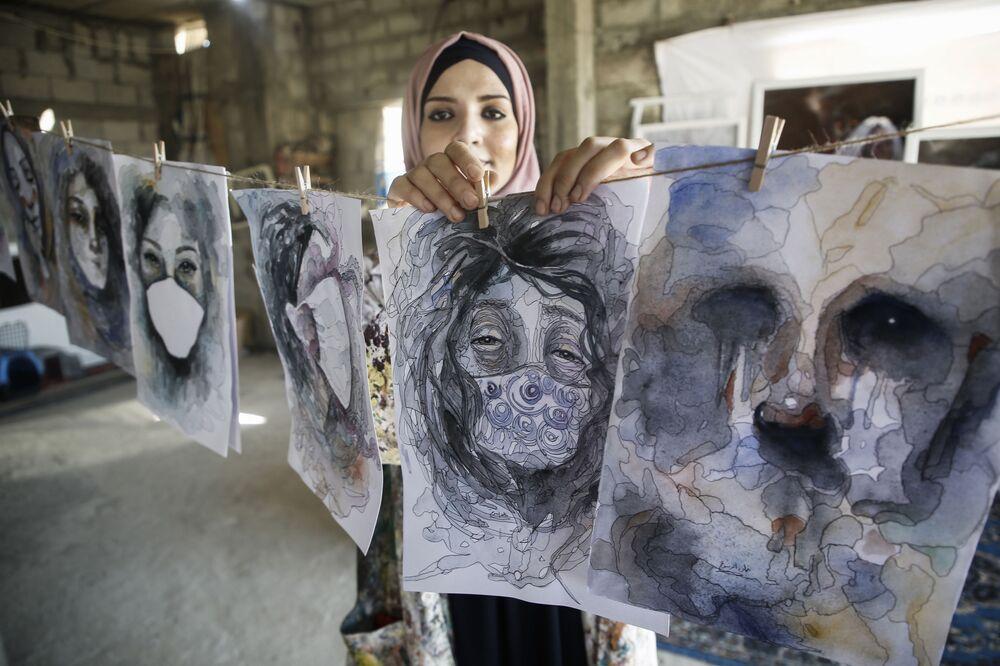 الفنانة الفلسطينية خلود الدسوقي تعلق لوحاتها خلال عملها في المنزل، أثناء الإغلاق التام في خان يونس، وسط قيود مشددة بسبب تفشي وباء كوفيد - 19، جنوب قطاع غزة، 12 أكتوبر 2020