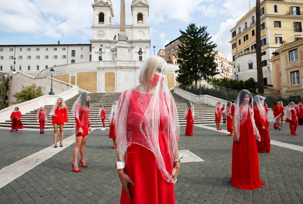 نساء يرتدين ملابس حمراء في سبانش ستيبس أثناء تسجيلهن مقطع فيديو لنشر التوعية بالعنف الاجتماعي القائم على التمييز الجنسي، قبل اليوم العالمي للقضاء على العنف ضد المرأة في 25 نوفمبر في روما، إيطاليا، 26 أكتوبر 2020