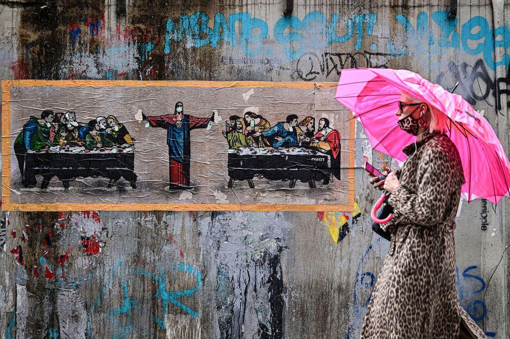 امرأة ترتدي كمامة تمر أمام لوحة جدارية جديدة لفنان الشارع الإيطالي TvBoy، بعنوان عشاء لستة أشخاص، مستوحاة من العشاء الأخير للفنان الإيطالي ليوناردو دا فينشي في جنوب مديمة ملاينو، إيطاليا 27 أكتوبر 2020
