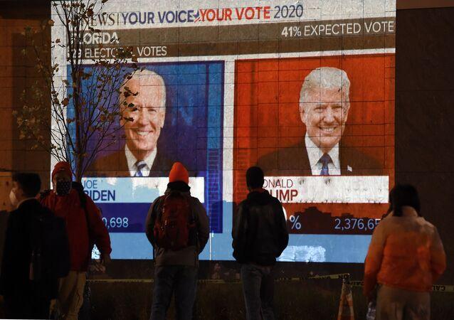 مواطنون يراقبون نتائج التصويت في الانتخابات الرئاسية الأمريكية 2020 على شاشة تلفاز كبيرة في أحد شوارع مدينة واشنطن، 3 نوفمبر 2020