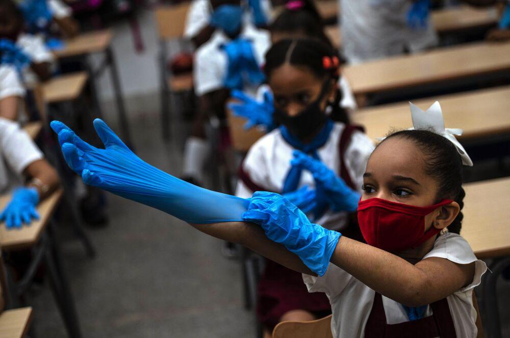 تلميذة ترتدي كمامة وقفازات كإجراء احترازي وسط انتشار فيروس كورونا خلال الفصل الدراسي في هافانا، كوبا، 2 نوفمبر 2020