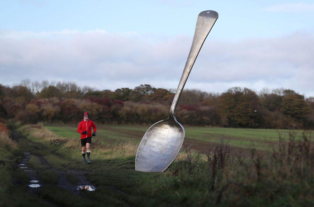 عداء يركض أمام تمثال الملعقة الضخمة في كراملينغتون، بريطانيا، 3 نوفمبر 2020