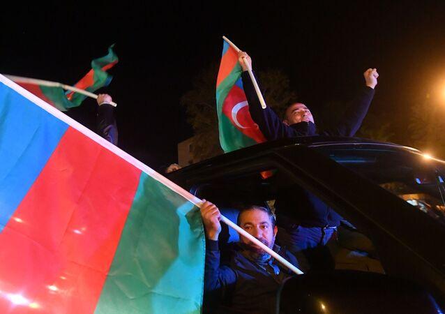 متظاهرون في أذربيجان يحتفلون بعد توقيع الرئيس الأذربيجاني، إلهام علييف، اتفاقا مع قادة أرمينيا وروسيا بشأن وقف الأعمال القتالية في ناغورني قره باغ، 10 نوفمبر 2020