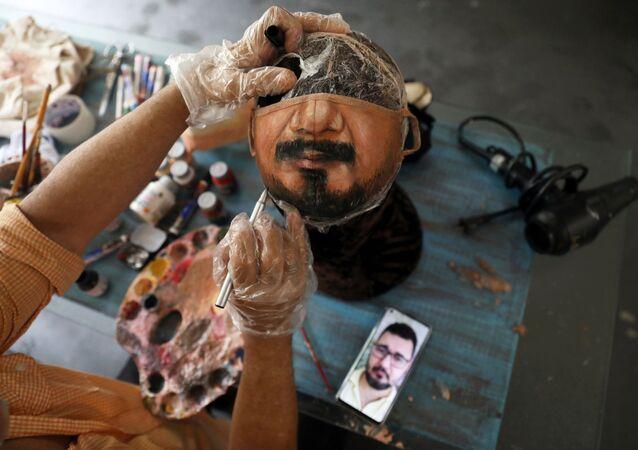 الفنان التشكيلي البرازيلي، خورخي سيلفا روريز، يرسم قناعًا وقائيًا بناءا على طلب الزيون، حيث ينظر إلى صورة الرجل على هاتفه الخلوي، وبعمل في منزله في ريو دي جانيرو، وسط تفشي مرض فيروس كورونا (كوفيد-19) في البرازيل، 10 نوفمبر 2020.
