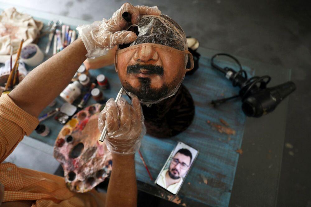 الفنان التشكيلي البرازيلي، خورخي سيلفا روريز، يرسم قناعًا وقائيًا بناءا على طلب الزيون، حيث ينظر إلى صورة الرجل على هاتفه الخلوي، ويعمل في منزله في ريو دي جانيرو، وسط تفشي مرض فيروس كورونا (كوفيد-19) في البرازيل، 10 نوفمبر 2020.
