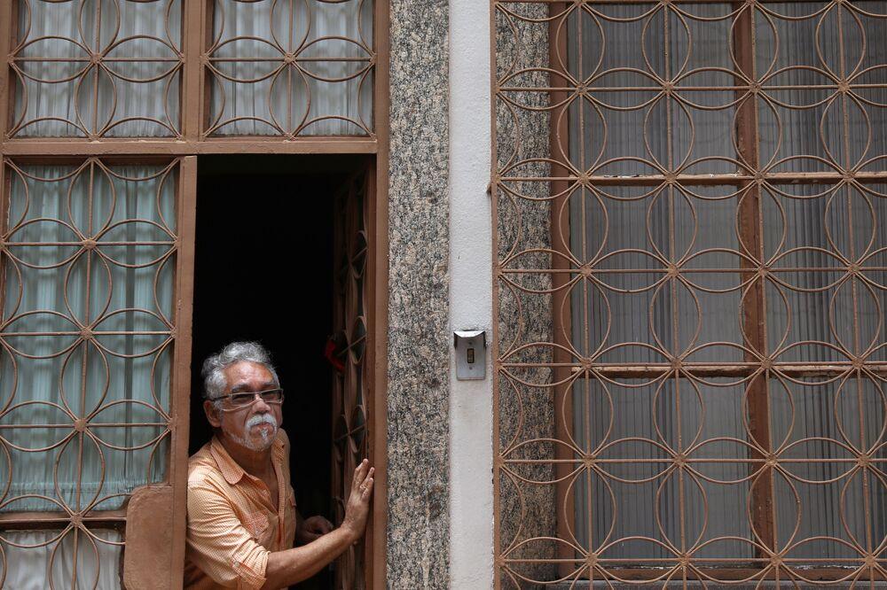 الفنان التشكيلي البرازيلي، خورخي سيلفا روريز، يطل من منزله في ريو دي جانيرو، مرتديا قناعاً من تصميمه وسط تفشي مرض فيروس كورونا (كوفيد-19) في البرازيل، 10 نوفمبر 2020.