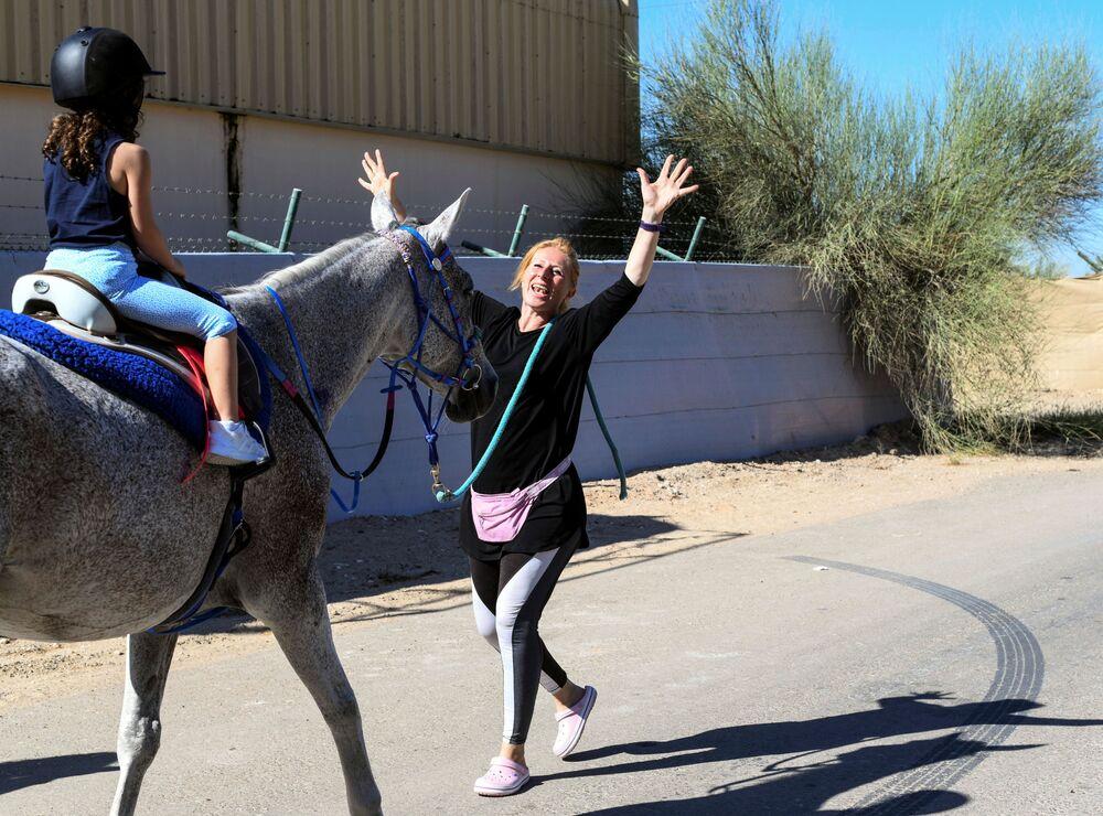 ياسمين السيد، مؤسِّسة برنامج Ride to Rescue، تقدم دروسًا في ركوب الخيل لفتاة في نادي مندرة للفروسية في أبو ظبي، الإمارات العربية المتحدة، 21 أكتوبر 2020