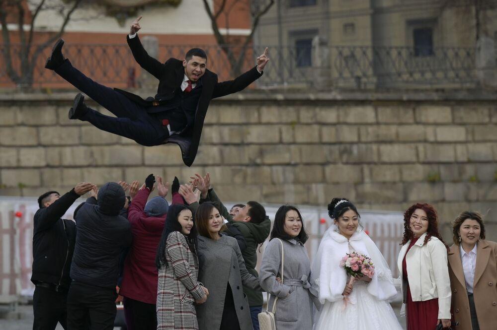 يحتفل المتزوجون حديثًا بزفافهم محاطين بأصدقائهم في الساحة الحمراء في موسكو، وسط استمرار انتشار وباء فيروس كورونا، 11 نوفمبر 2020،.