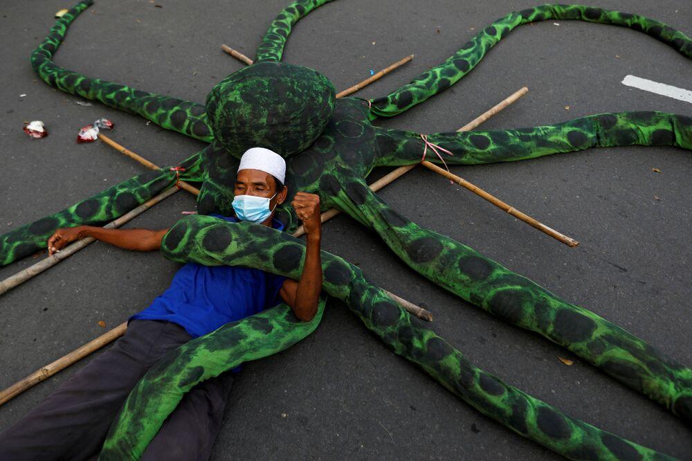 صياد يرتدي كمامة مستلقيا على أخطبوط صناعي، خلال احتجاج على إصلاحات الحكومة فيما يخص العمل في مشروع قانون خلق فرص العمل في جاكرتا، إندونيسيا، 10 نوفمبر  2020.