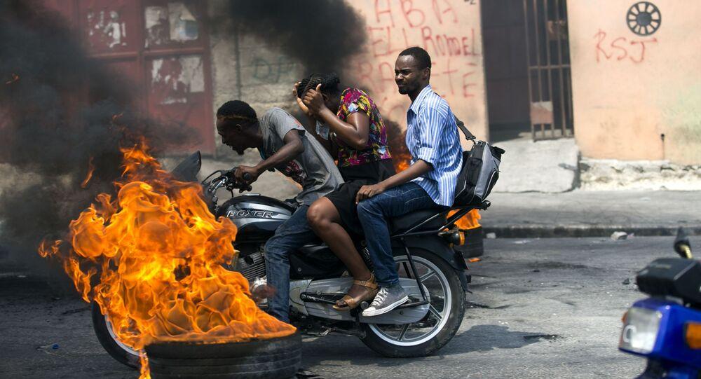 دراجة نارية أجرة تمر بجانب إطار محترق في بورت أو برنس، هاييتي