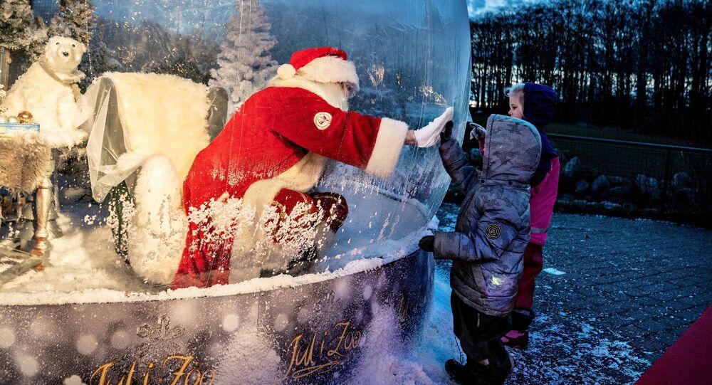 شخص يرتدي زي بابا نويل يلتقي بأطفال أثناء جلوسه في فقاعة سانتا كلوز أثناء افتتاح موسم الكريسماس في حديقة حيوانات ألبورغ وسط تفشي مرض فيروس كورونا (كوفيد-19)، في آلبورغ، الدنمارك، 13 نوفمبر 2020.
