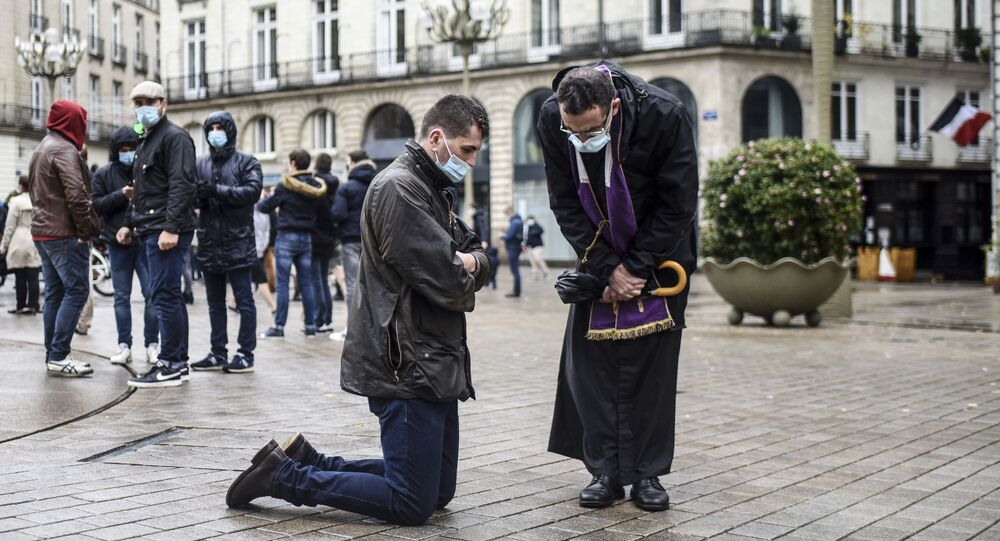 كاهن يستمع إلى اعتراف أحد المواطنين في الشارع، خلال تجمع للمصلين للدعوة إلى إعادة فتح أماكن العبادة أثناء الإغلاق العام بسبب انتشار فيروس كورونا (كوفيد-19) في نانت، غرب فرنسا 15 نوفمبر 2020