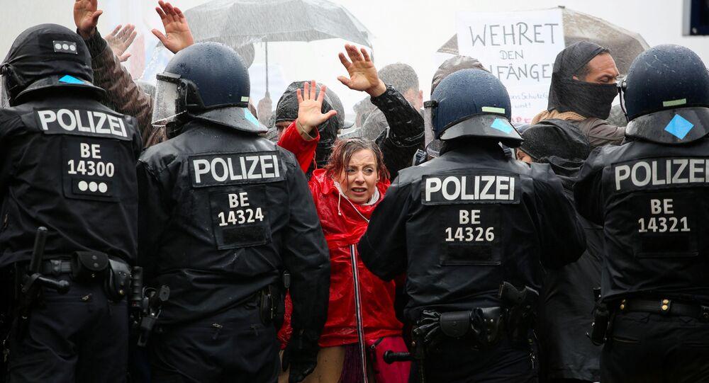متظاهرون يرفعون أيديهم أمام ضباط الشرطة خلال احتجاجات ضد قيود الحكومة الألمانية التي فرضتها لاحتواء وباءكورونا (كوفيد-19) ، بالقرب من بوابة براندنبورغ في برلين، 18 نوفمبر 2020.