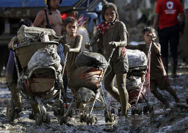 أطفال يدفعون عربات أطفال المليئة بالممتلكات التي استعادوها من منازلهم المتضررة في قريتهم عقب إعصار فامكو في رودريغيز، مقاطعة ريزال، الفلبين، 17 نوفمبر 2020.