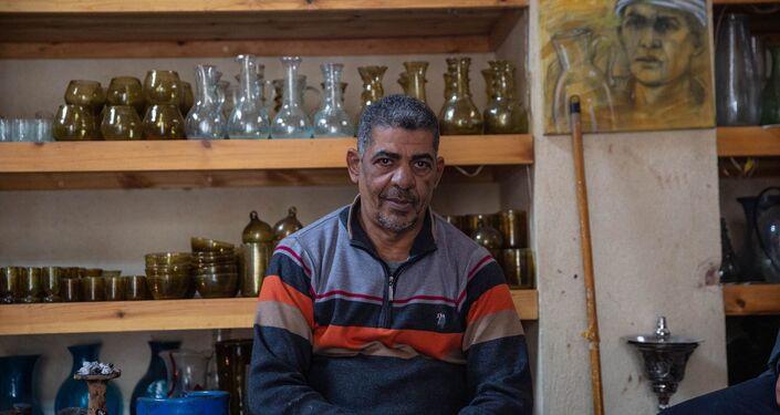 خالد علي صاحب ورشة صناعة الزجاج اليدوي، يجلس أمام بعض منتجاته