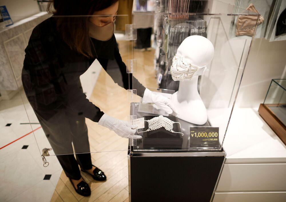 موظفة في شركة Cox Co، الشركة المشغلة لمتجر متخصص في بيع أقنعة الوجه Mask.com، تعرض قناع وجه فاخر مصنوع من حوالي 330 لؤلؤة، معروض للبيع مقابل مليون ين (9640 دولار)، وسط تفشي  فيروس كورونا (كوفيد -19) في طوكيو، اليابان، 25 نوفمبر/ تشرين الثاني 2020.