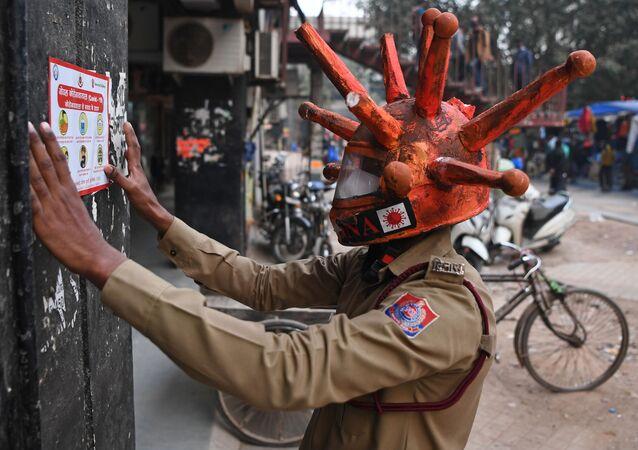 متطوع في الدفاع المدني يرتدي خوذة مستوحاة من فيروس كورونا، يلصق لافتة على الحائط أثناء مشاركته في حملة توعية في أحد الأسواق في نيودلهي، في الهند 25 نوفمبر 2020