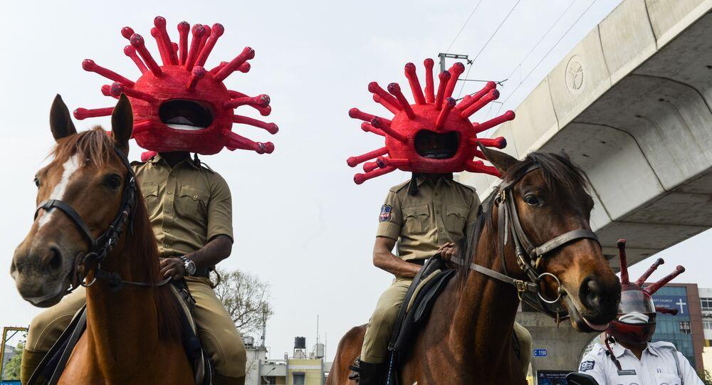 ضابطا شرطة، سودهاكار يادار، يقومان بدورية،ر ويرتديان قناعا مصمما على شكل فيروس كورونا على طريق، بهدف التوعوية، خلال الإغلاق الوطني التام فرضته الحكومة كإجراء وقائي لمنع تفشي مرض الفيروس التاجي كوفيد-19، في حيدر آباد، الهند 2 أبريل 2020.