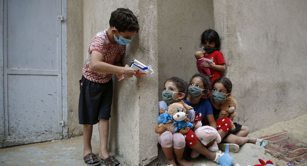 أطفال فلسطينيون يرتدون كمامات بسبب وباء فيروس كورونا كوفيد-19، يلعبون خارج منزلهم في مدينة غزة، 8 سبتمبر  2020.