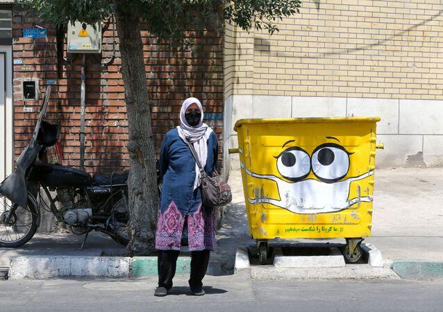 امرأة تقف بجوار سلة القمامة المرسوم عليها كمامة، في إطار حملة لنشر الوعي حول جائحة كورونا، في حي جنوبي بالعاصمة الإيرانية طهران في 18 يوليو 2020.