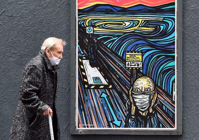 مسن يرتدي كمامة يسير من أمام رسم غرافيتي على جدار مستوحاة من العمل الفني الشهير الصرخة للفنان النرويجي إدوارد مونك، ولكن الشخصية أيضا ترتدي كمامة، في غلاسكو،  2 سبتمبر 2020