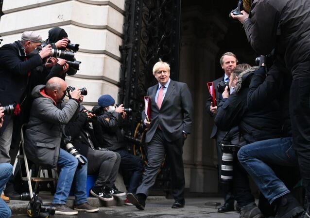 رئيس الوزراء البريطاني بوريس جونسون يعود إلى 10 داونينغ ستريت في لندن، 8 ديسمبر 2020، بعد ترأسه الاجتماع الأسبوعي لمجلس الوزراء الذي عقد في مكتب الخارجية والكومنولث والتنمية القريب. أشادت بريطانيا يوم الثلاثاء الماضي بنقطة تحول في الحرب ضد الجائحة، حيث شرعت بأكبر برنامج لتطعيم المواطنين في تاريخ البلاد بلقاح جديد ضد كوفيد -19.