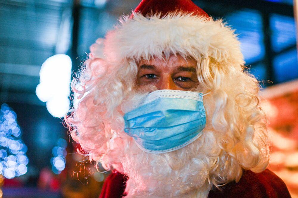 بابا نويل يرتدي كمامة ويرحب بالزوار عند الدخول إلى سوق عيد الميلاد في محطة الطاقة النووية القديمة في كالكار، غرب ألمانيا11 ديسمبر 2020