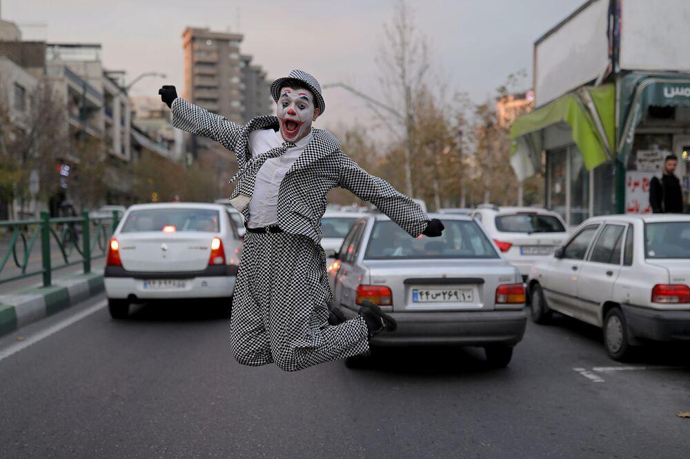 محمد، فنان شوارع إيراني يرتدي زي شخصية الجوكر، يقف مع أعضاء فرقة مسرحية أثناء عرض ترفيهي للمواطنين، وسط تفشي كورونا (كوفيد-19) في طهران، إيران، 12 ديسمبر 2020