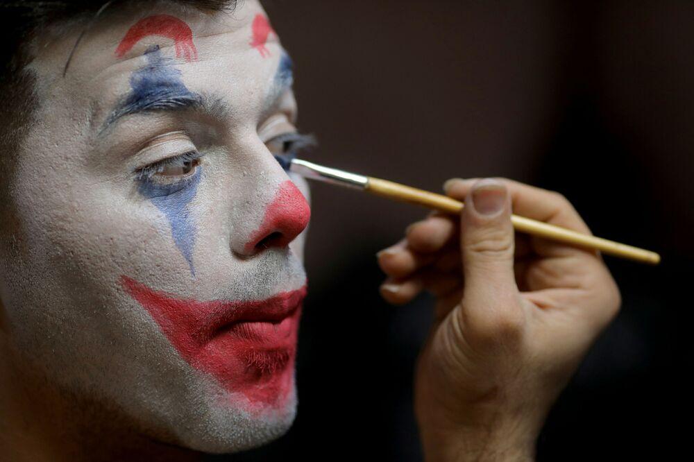 محمد، فنان شوارع إيراني، يضع ماكياج الجوكر قبل الخروج مع فرقته المسرحية إلى عرض ترفيهي في إحدى شوارع مدينة  طهران، إيران، 12 ديسمبر 2020